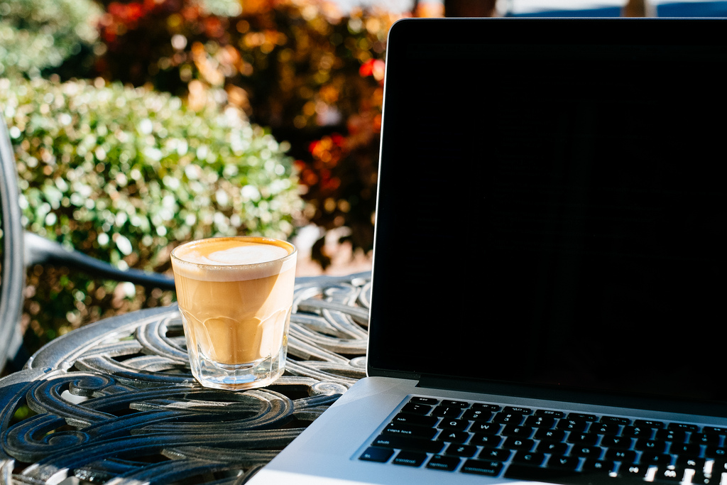 Language Ninja: What Makes a Good Translation? Photo of a garden table with a laptop and a glass of cappuccino.