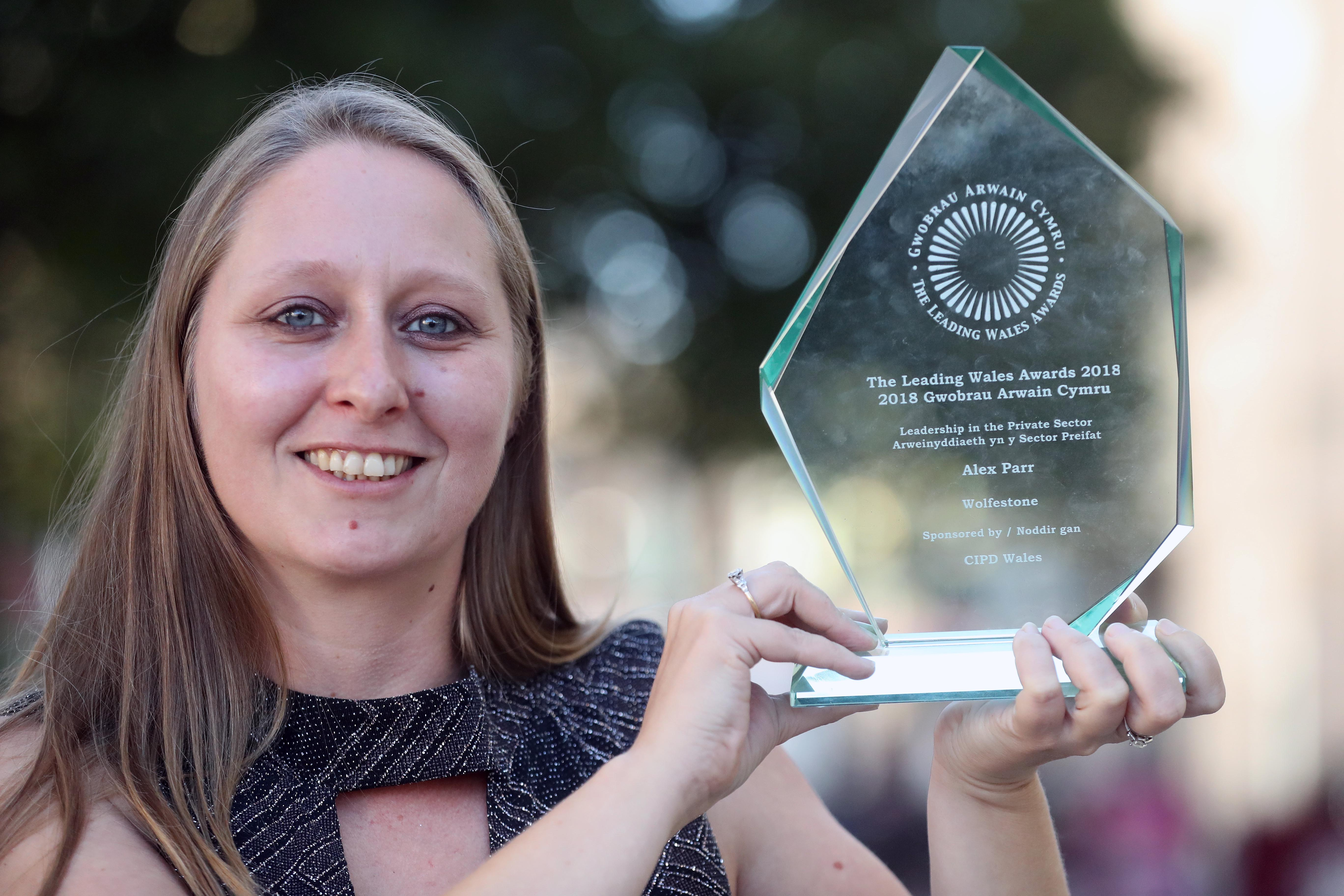 Image of Wolfestone Managing Director, Alex Parr, holding the Leadership in the Private Sector award.