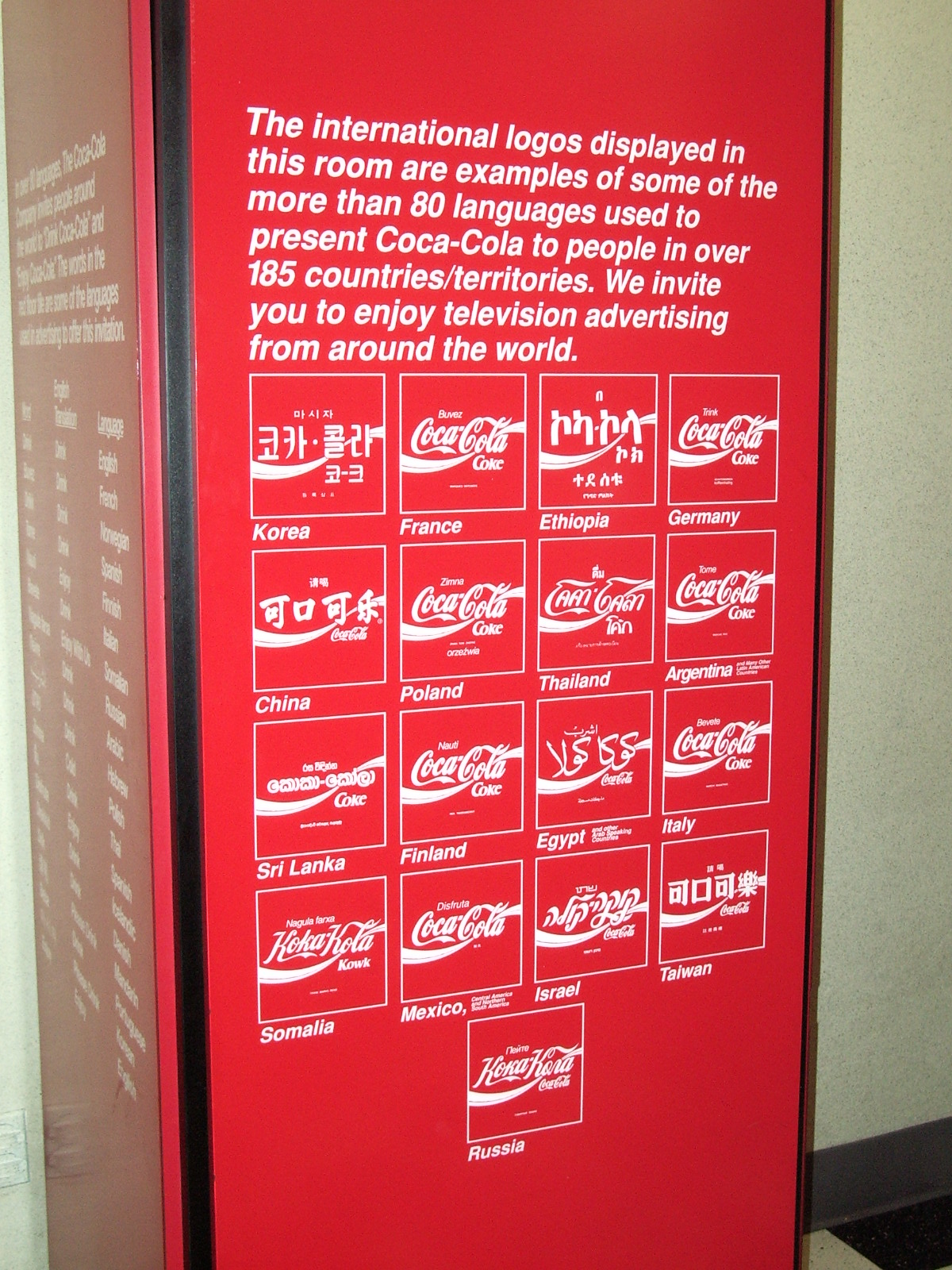 Sign displaying Coca Cola brand logos in different languages