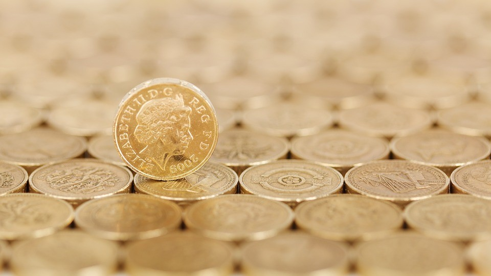 Pound coins spread about along a surface indicating the fall of the GBP after Brexit