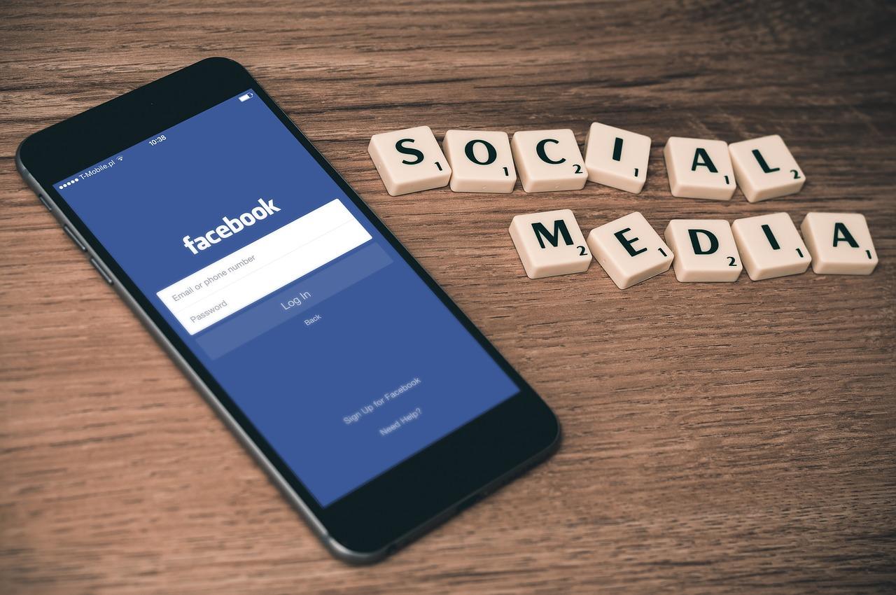 Social Media written with scrabble tiles next to a phone on the Facebook app. (International Social Media Marketing)