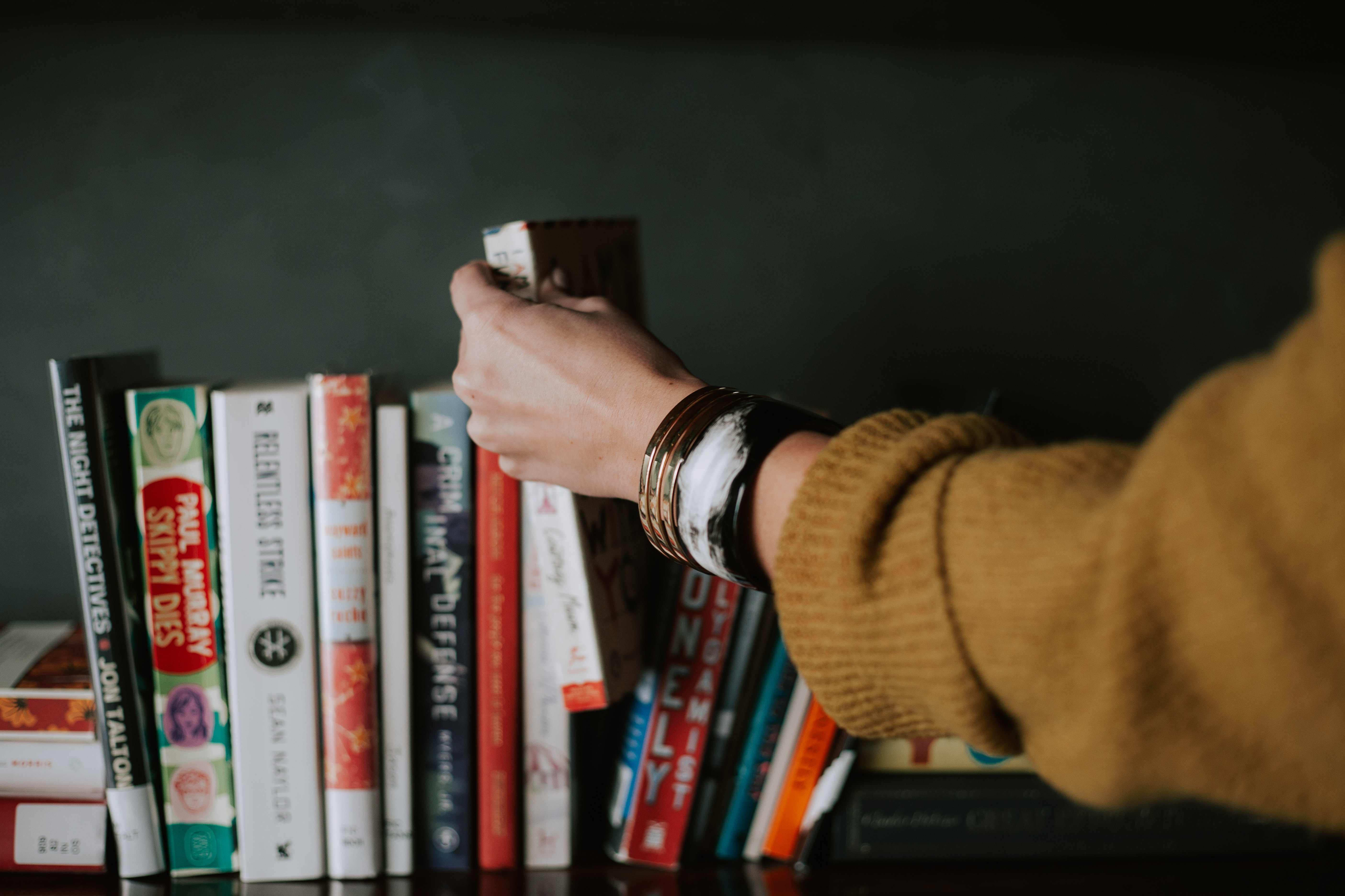 Image of a book shelf, with someone taking a book out. Depicts the theme of the article, literary translation.