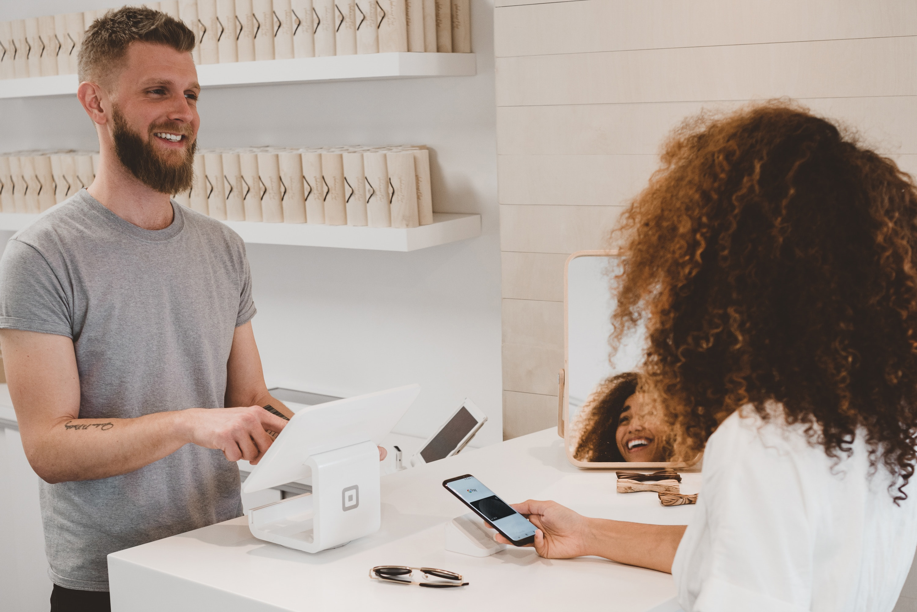 Customer smiling and paying with her phone to a man.