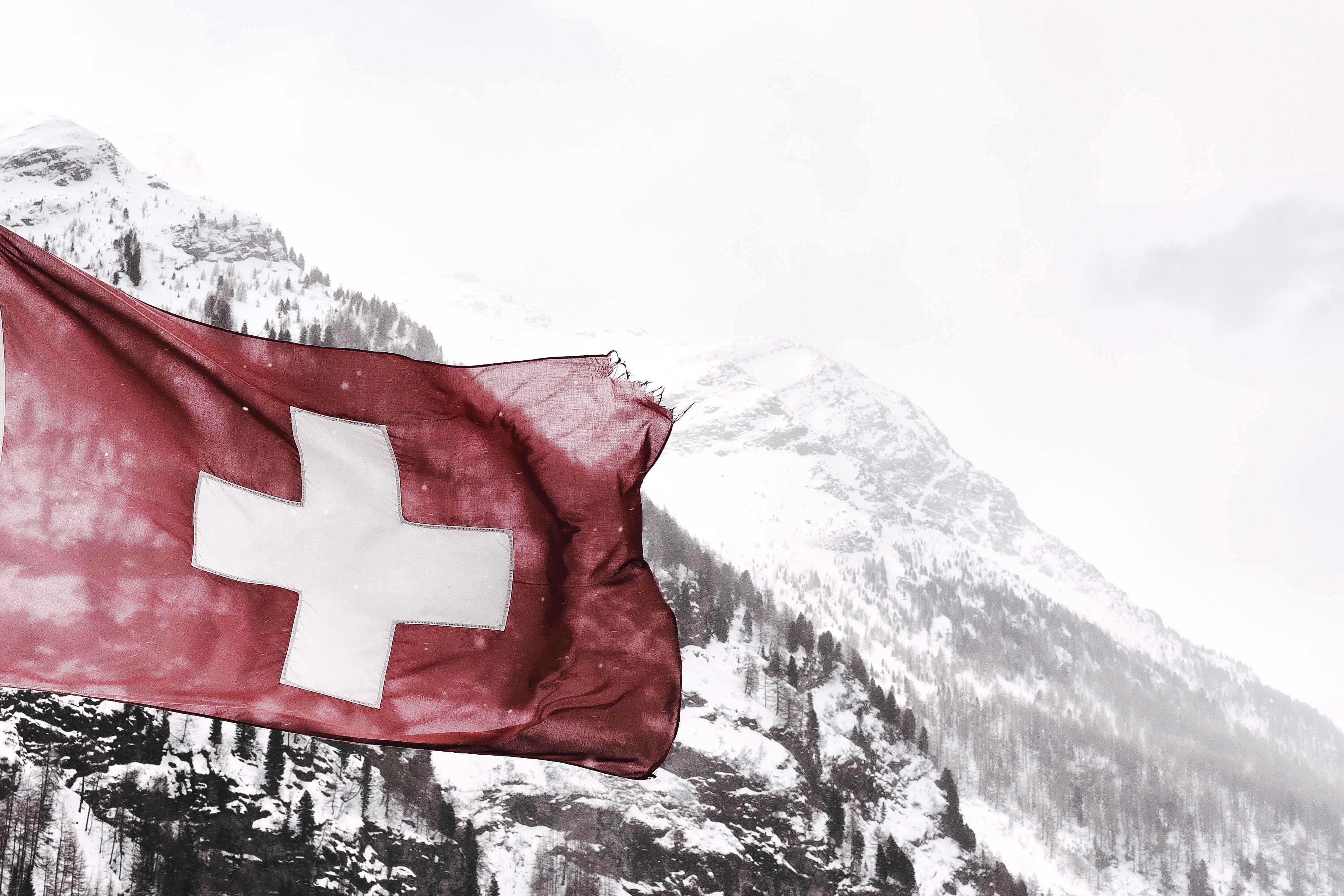 The Swiss flag flying with a mountain backdrop.