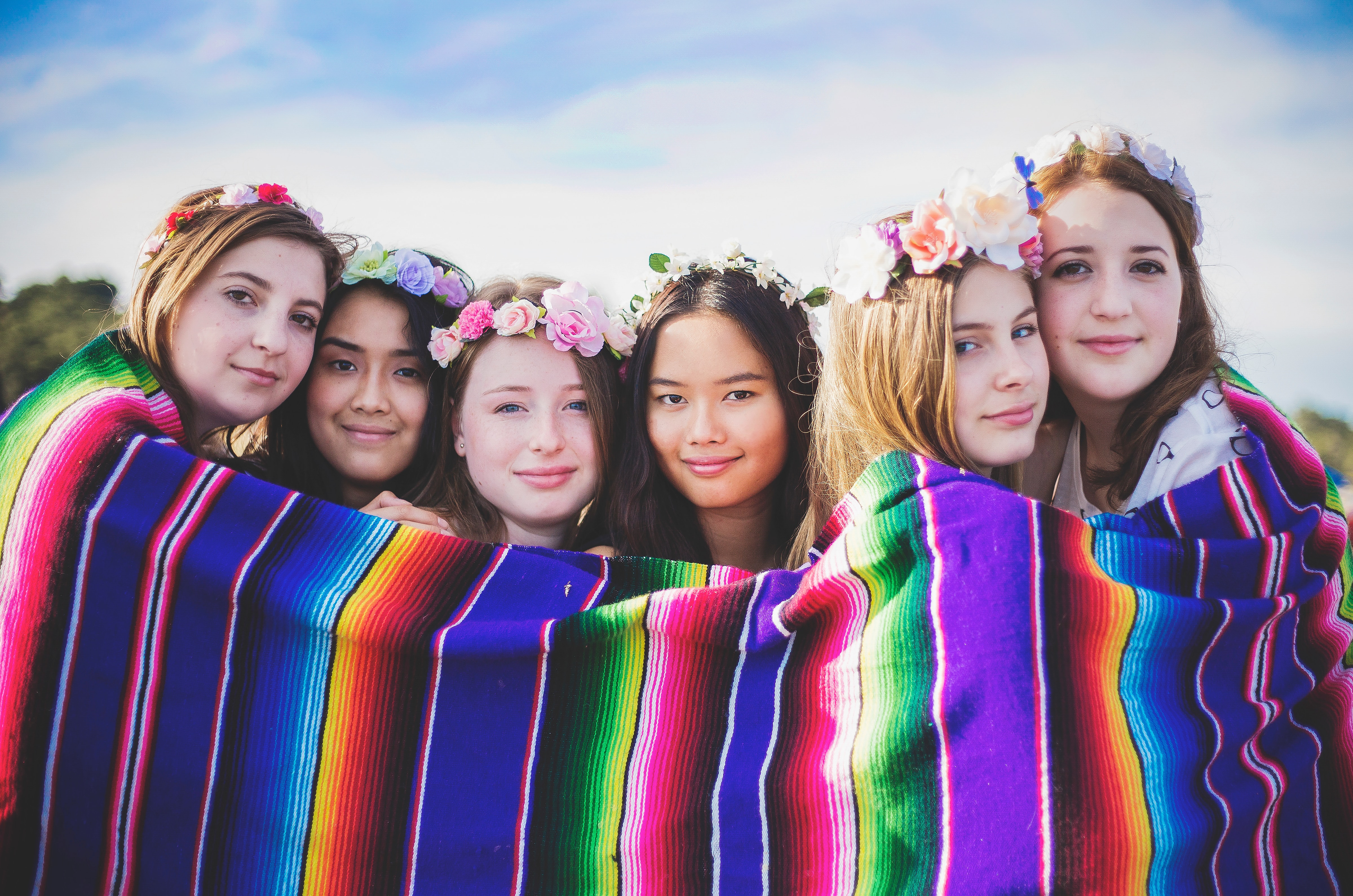 Image of six multinational female youths standing behind a multicoloured blanket