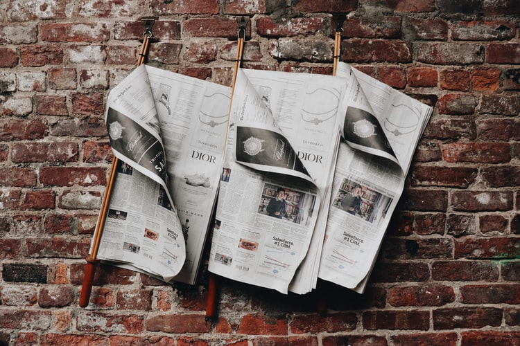 Three open newspapers on a wall
