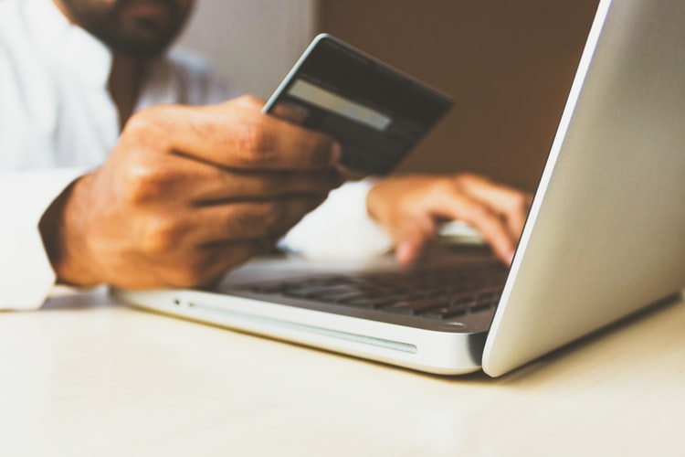 Man making purchase online holding credit card
