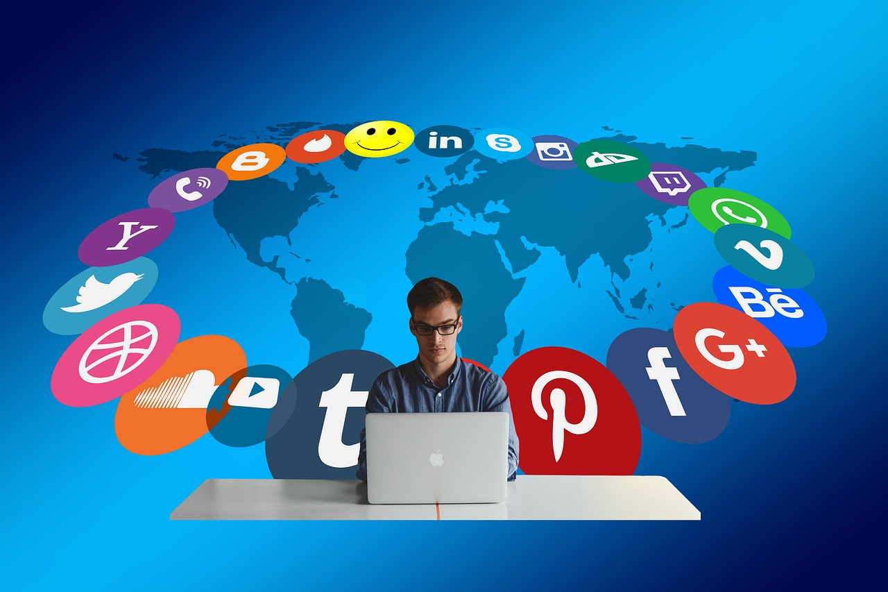 Man sitting at a laptop with social media logos behind him and map of the world.