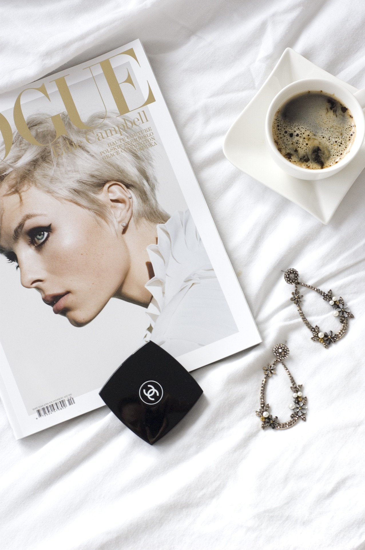 Still life featuring copy of Vogue magazine with accessories and a cup coffee